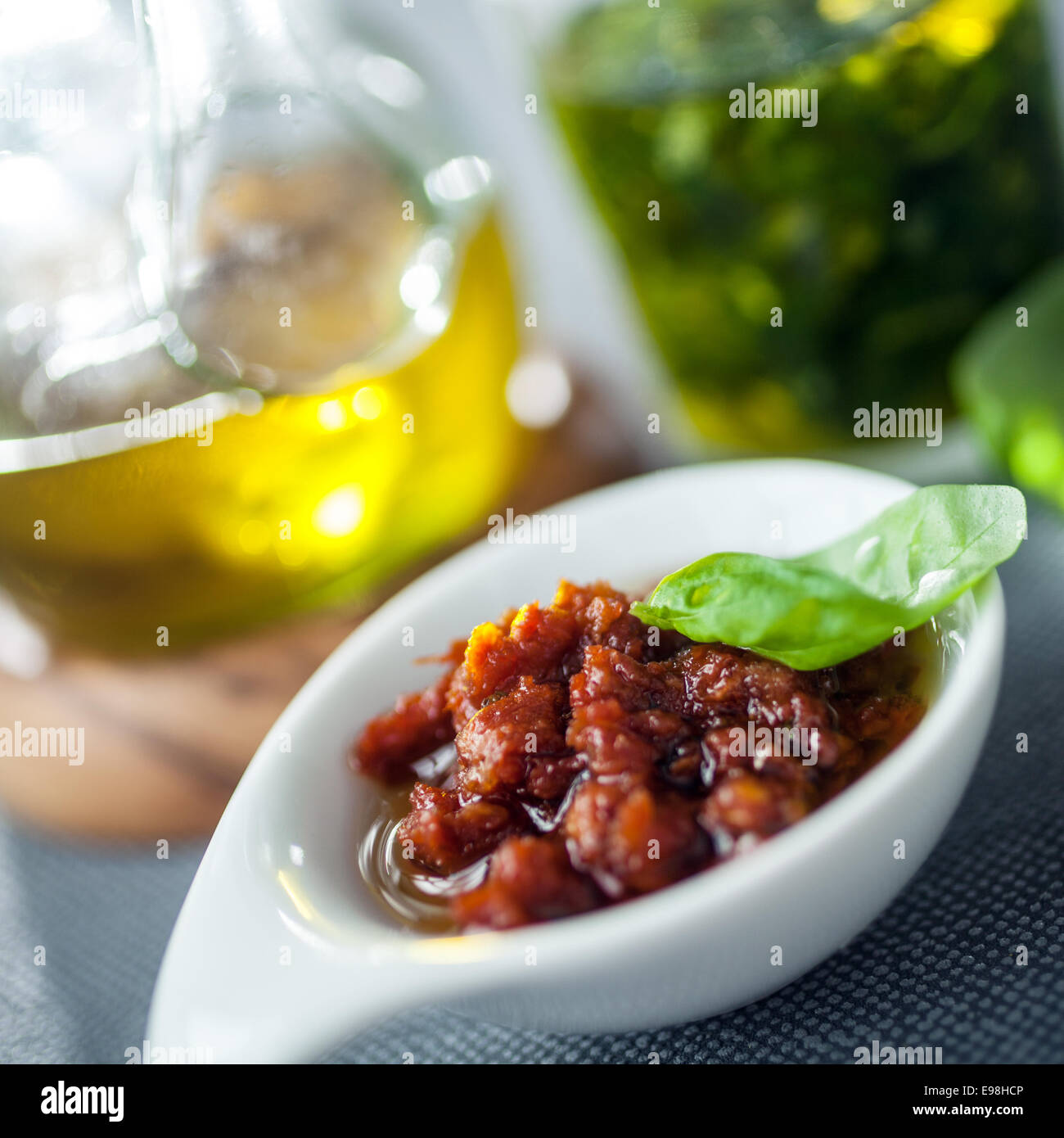 Savory accompaniments served in a restaurant with a bowl of piquant chutney or spicy dip, virgin olive oil, and - Stock Image