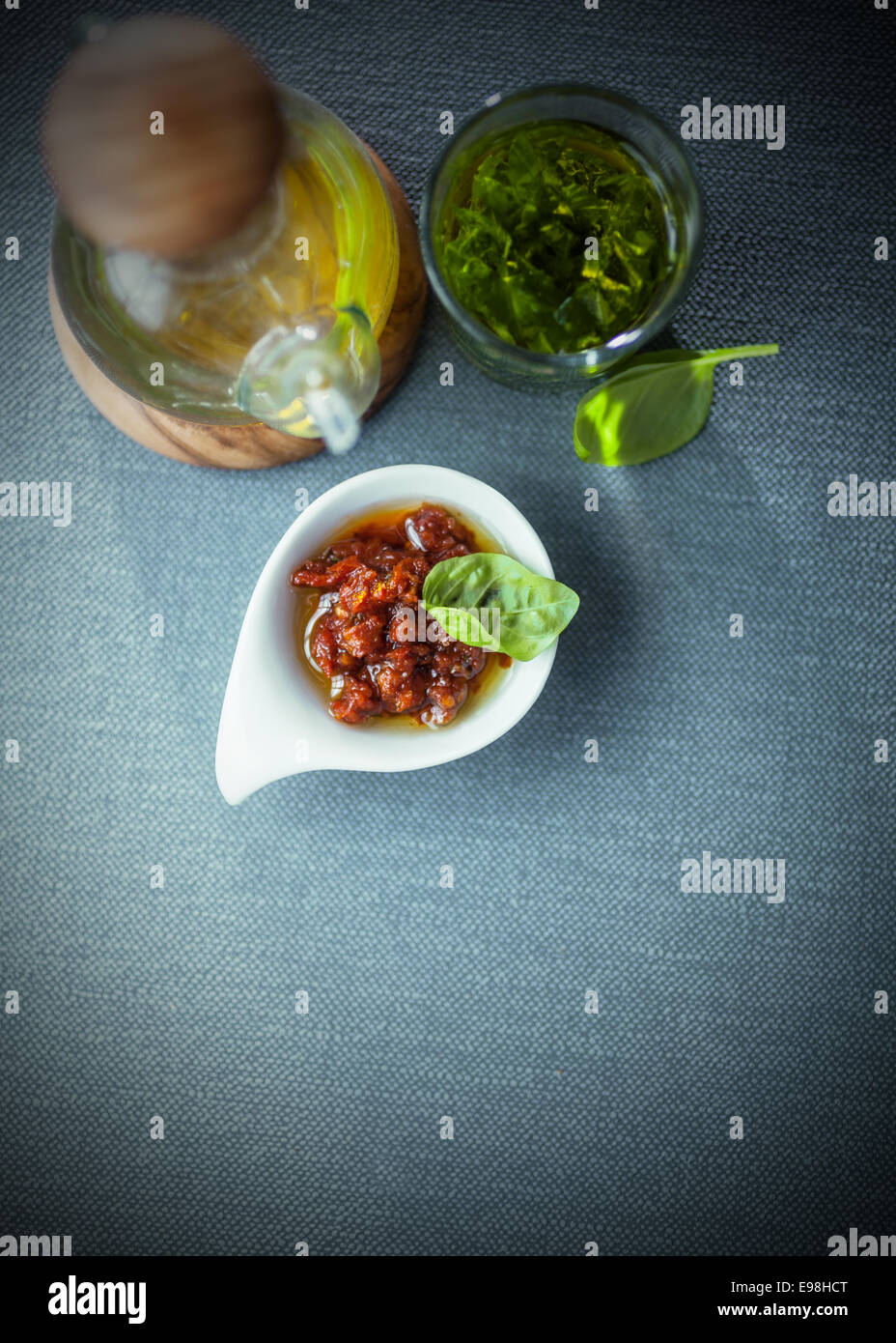 Savory condiments in a restaurant with a spicy dip, virgen olive oil in a decanter and fresh basil pesto, overhead - Stock Image