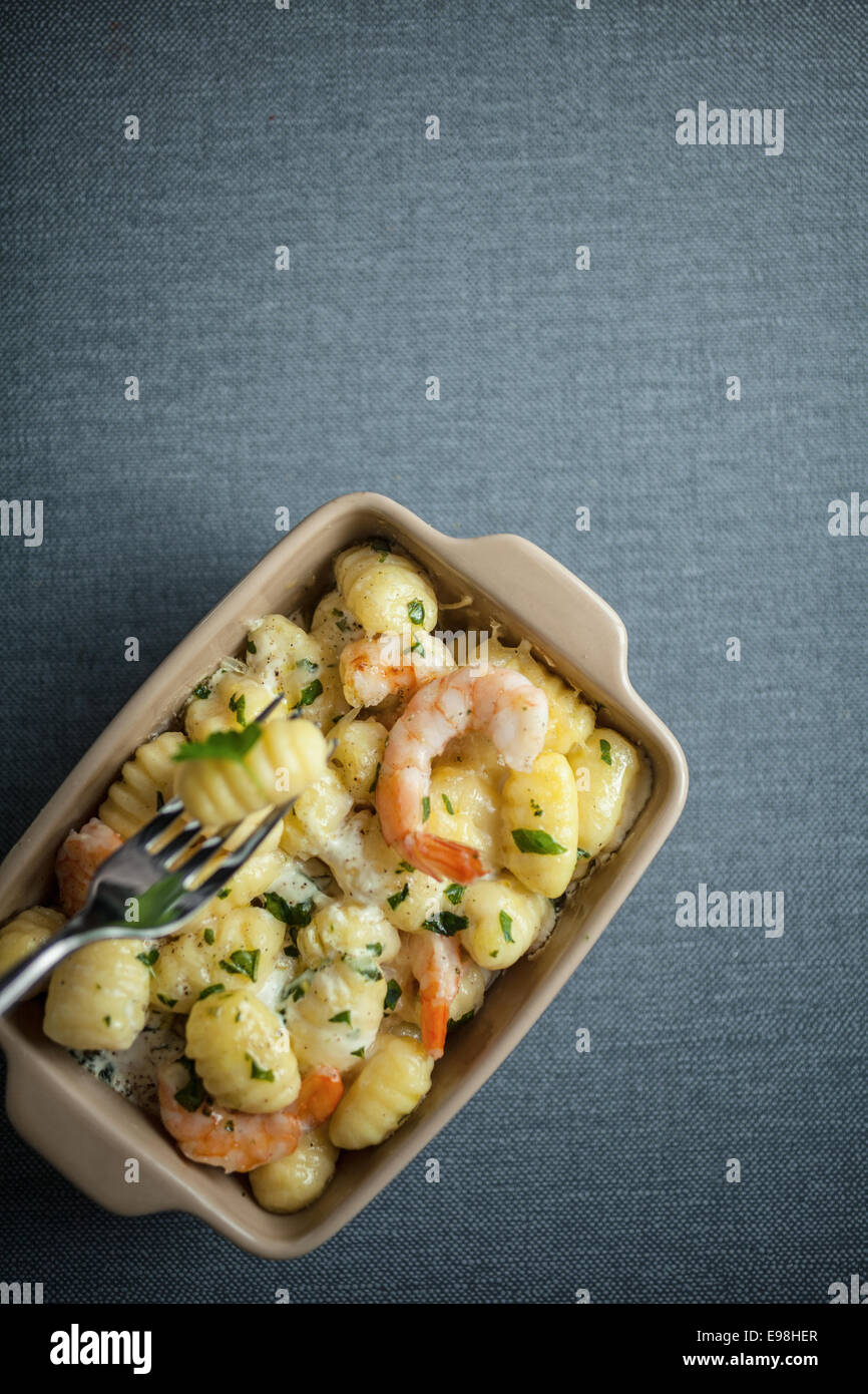 Overhead view of a dish of Italian gnocchi pasta, or semolina dumplings, with shrimps and fresh herbs with one pasta Stock Photo