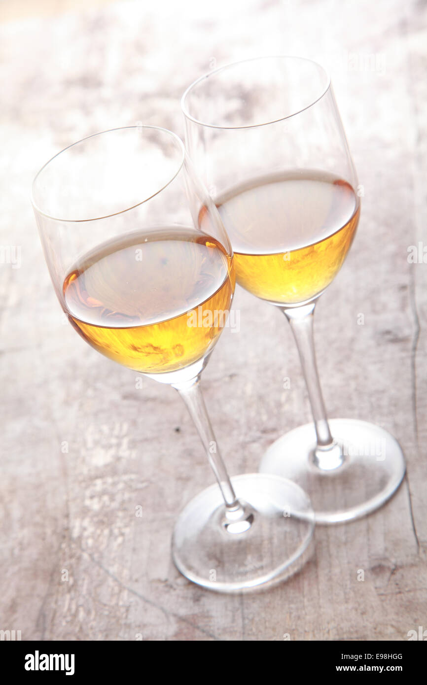 Two glasses of white sherry wine standing touching viewed high angle on a rustic wooden garden table in sunlight Stock Photo