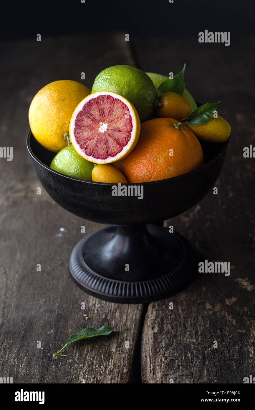 Pedestal bowl of assorted fresh citrus fruit with a halved blood orange displayed at the front on a rustic wooden - Stock Image