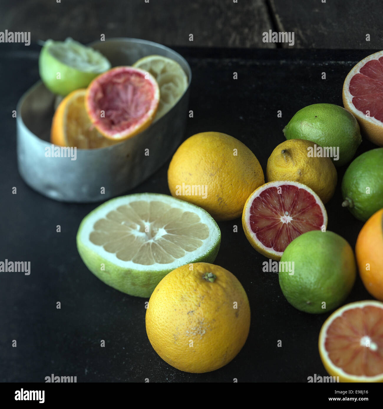 Juicing a selection of fresh citrus fruit with grapefruit, oranges, limes and lemons and a metal container with - Stock Image