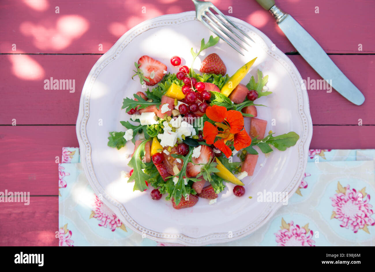 Strawberry pink flowers stock photos strawberry pink flowers stock tasty summer salad melon strawberry redcurrants and wild flowers on pink wooden background mightylinksfo