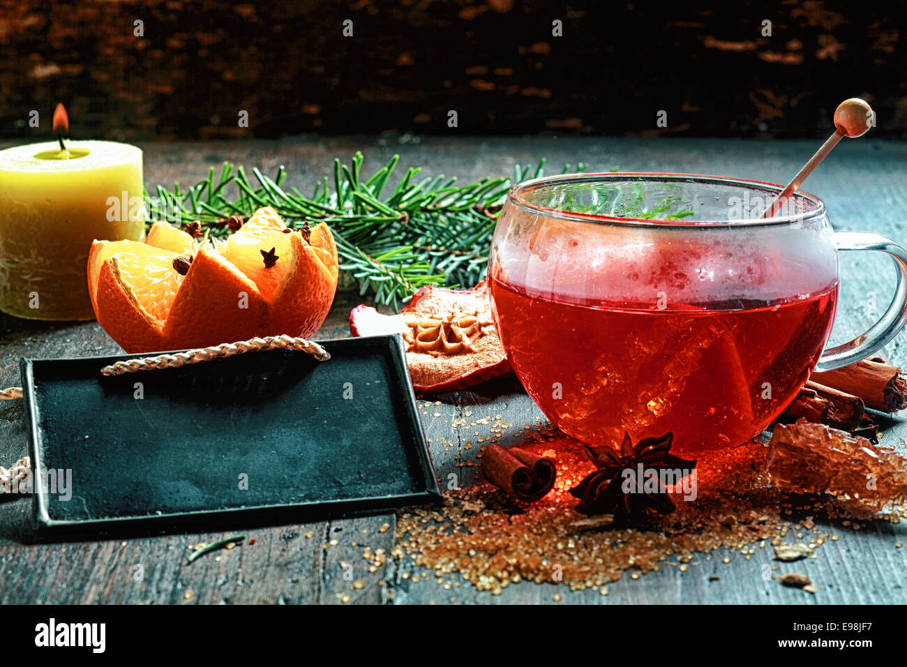 Christmas Eve spiced hot tea or gluhwein with crystallised sugar, a decorative orange and spices alongside a burning - Stock Image