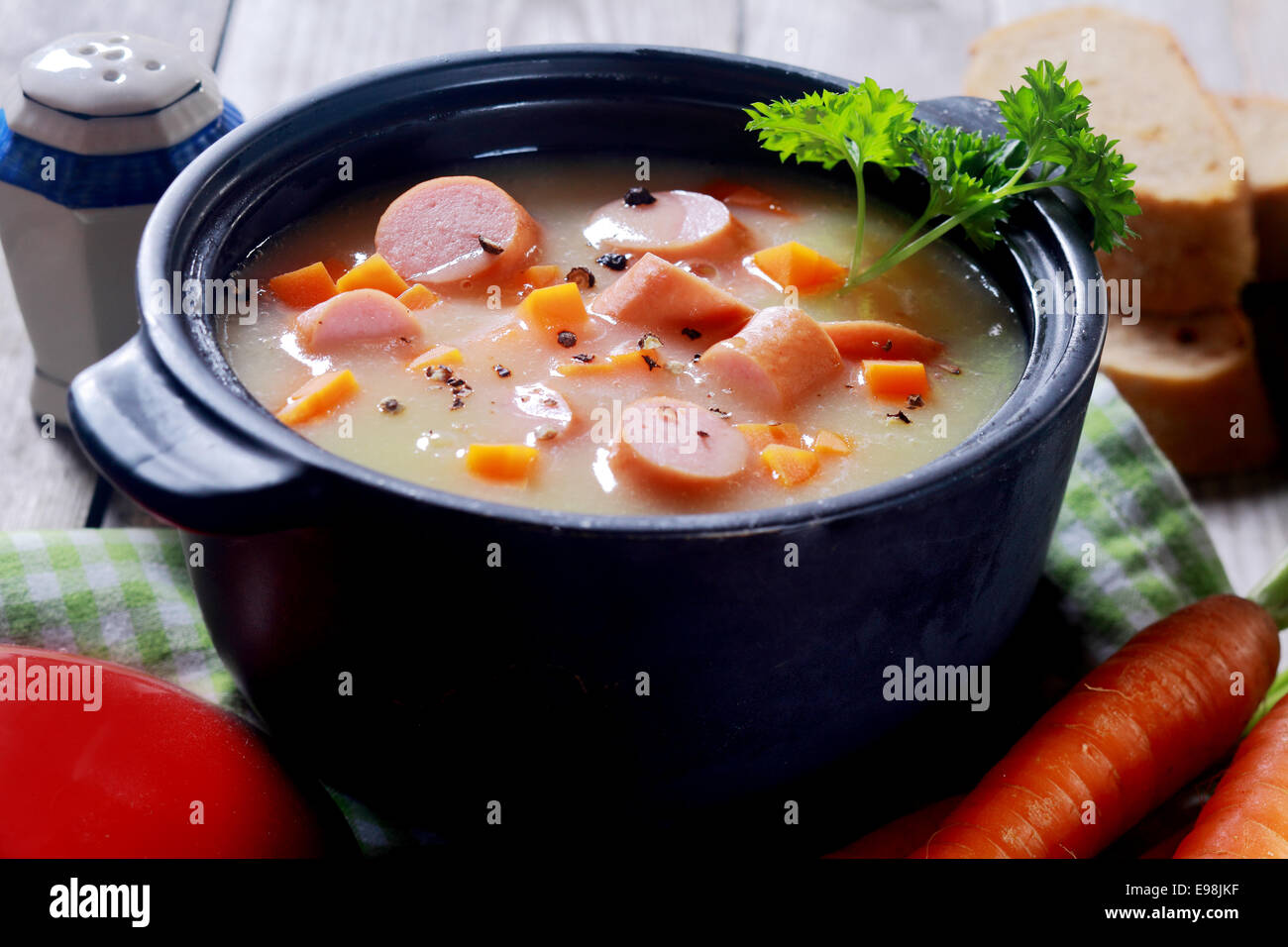 Close up Appetizing Creamy Soup Dish on Black Pot Placed on Wooden Table. - Stock Image