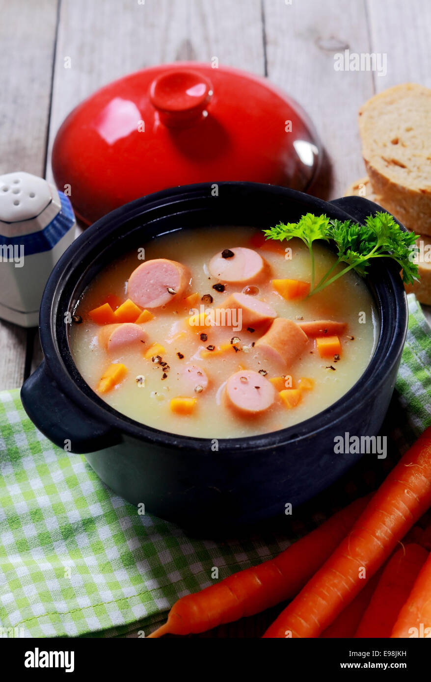 Close up Tasty Healthy Creamy Soup with Sausage on Black Pot Placed on Wooden Table. - Stock Image