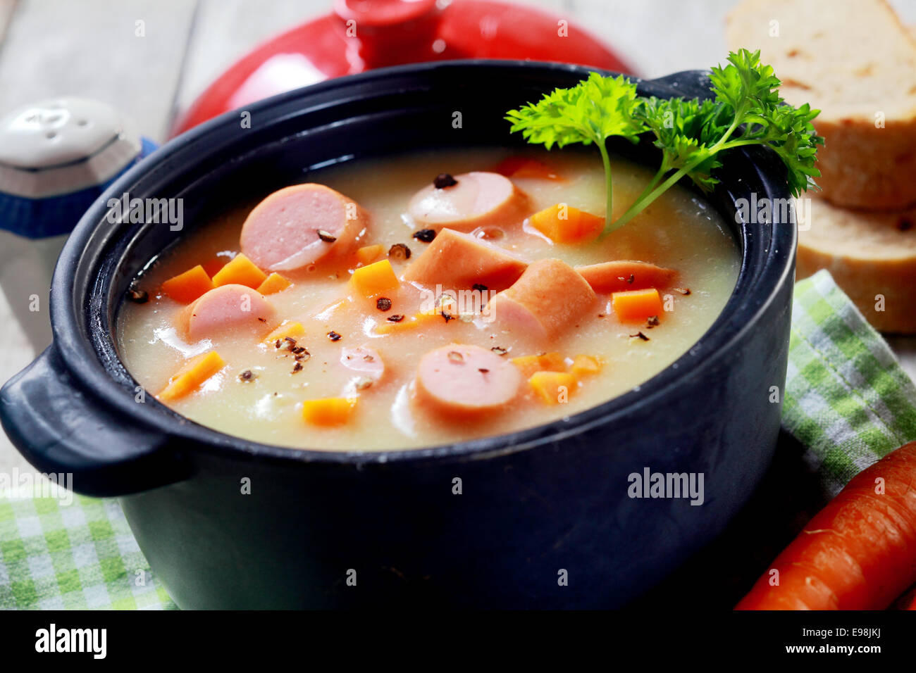 Close up Mouth Watering Hot Creamy Soup Dish with Sausage on Cloth at Wooden Table. - Stock Image