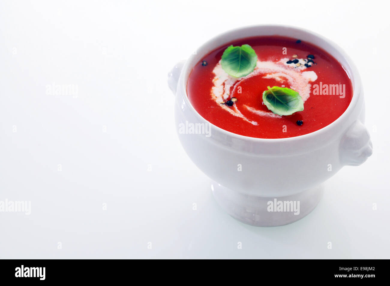 Tomato soup with a swirl of cream and fresh basil leaves seasoned with pepper in a white bowl over white with copyspace - Stock Image