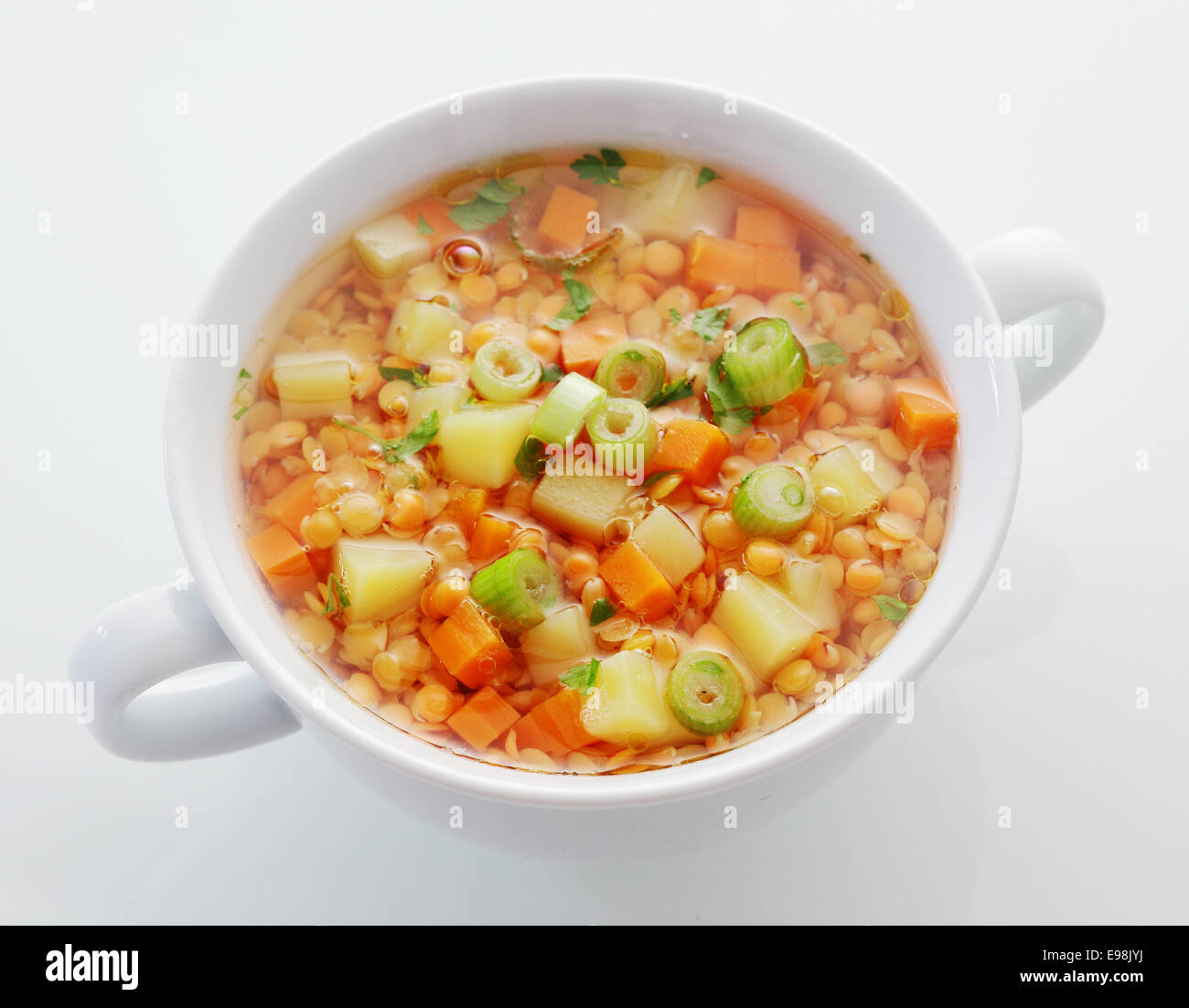 Wholesome bowl of lentil, carrot and leek soup rich in protein and dietary fiber, high angle view on white - Stock Image