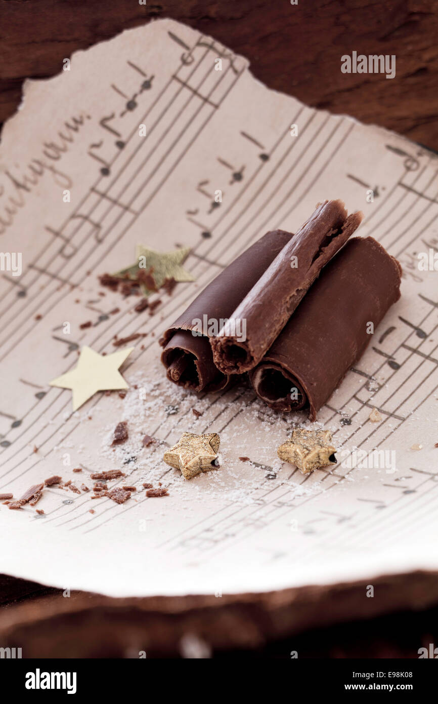 chocolate curls with golden stars and music paper - Stock Image