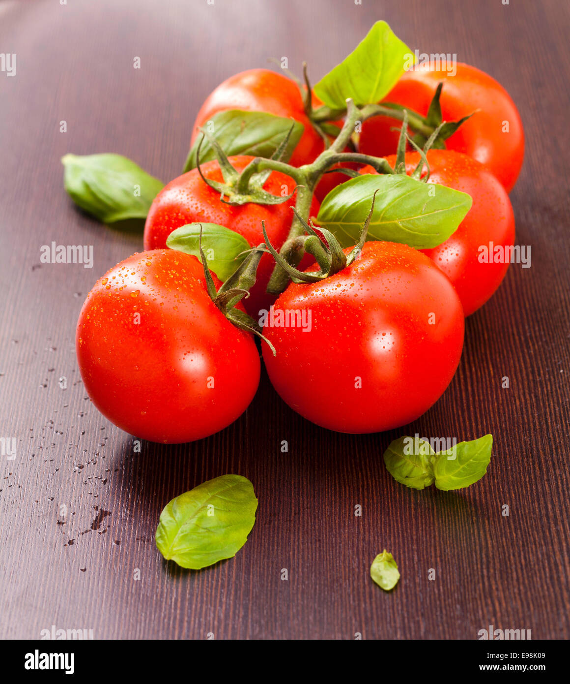 vine-ripened tomatoes with basil on a wooden plate Stock Photo
