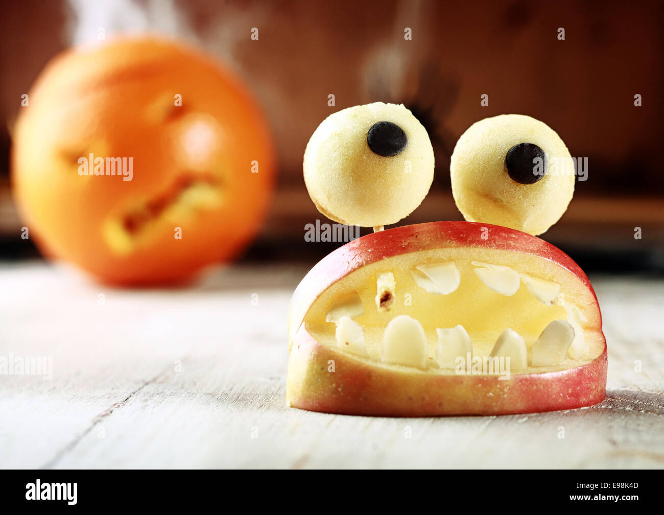 cute homemade halloween apple decoration of an open mouth with teeth topped with googly dough eyes on toothpicks for a scary but healthy favor to give