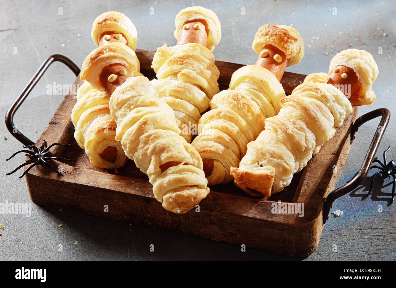five weiner mummies wrapped in pastry on tray for halloween party appetizer