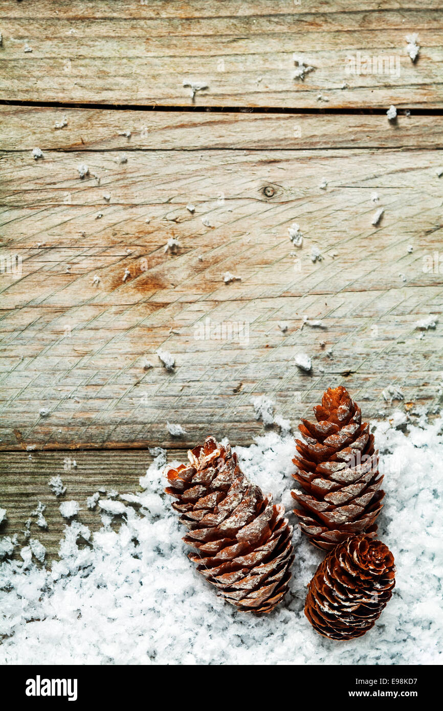 Pine Cone Rustic Christmas Background With Three Cones Nestling In Winter Snow On Old Weathered Wooden Boards Plenty Of Copyspace For Your Xmas Message