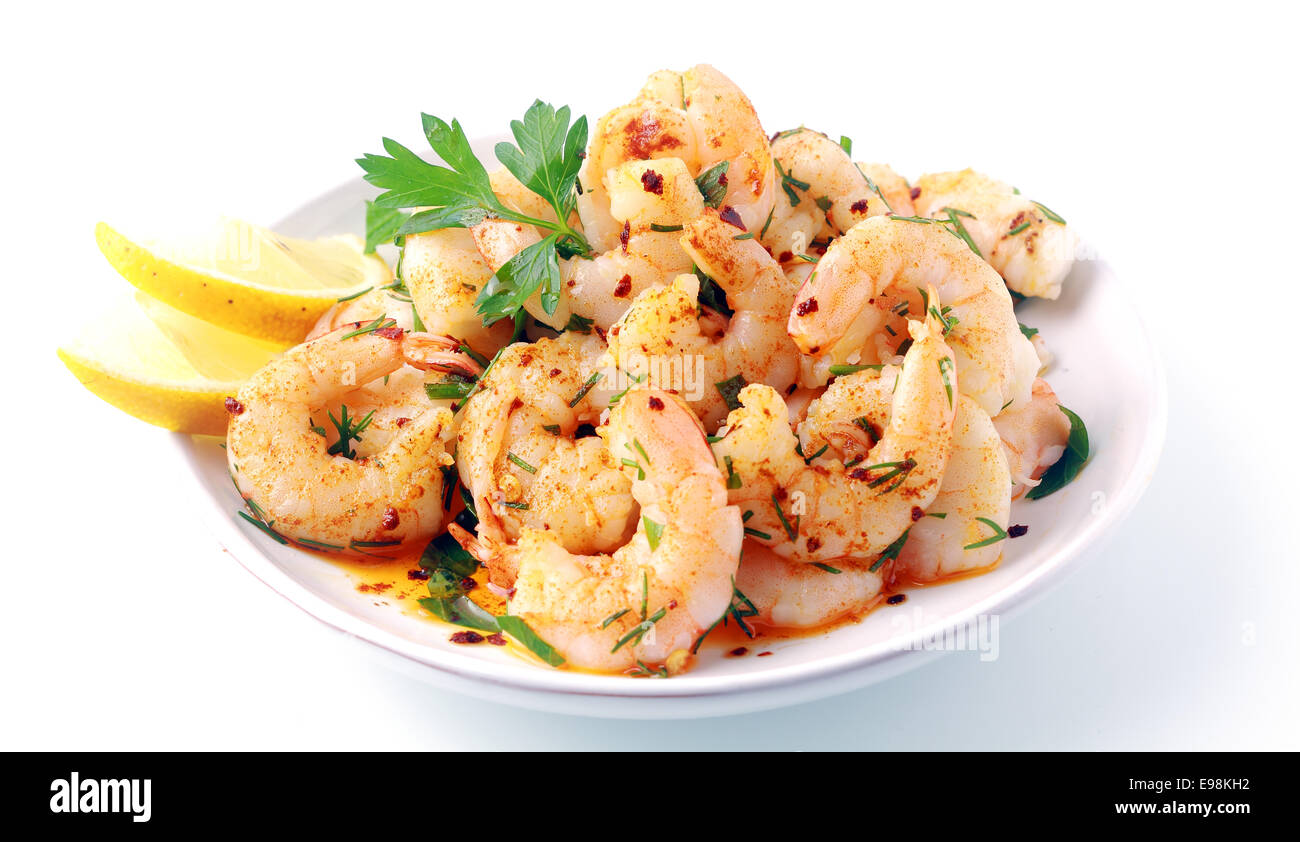 Seasoned savory pink prawns or shrimp tails grilled in fresh diced herbs and butter and served with slices of fresh - Stock Image