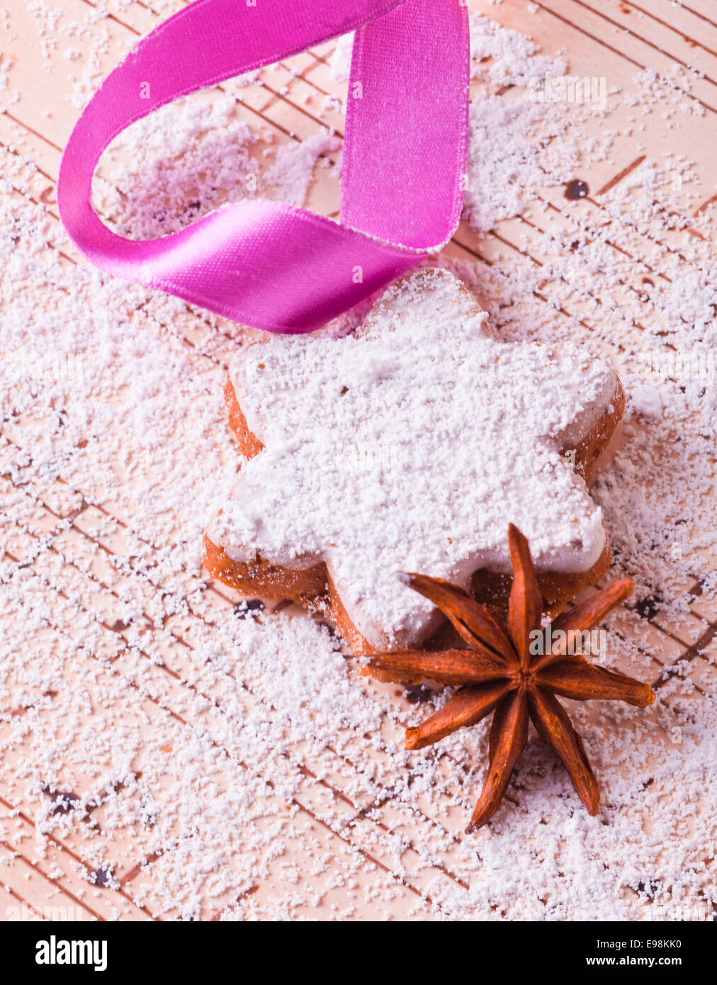 X-mas cookie with a pink bow and icing sugar and one anise - Stock Image