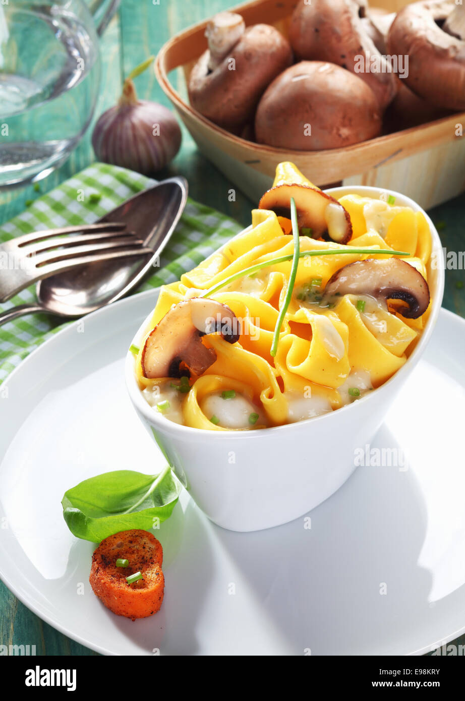 Boat-shaped dish of mushroom tagliatelle with a bowl of fresh mushrooms in the background. - Stock Image