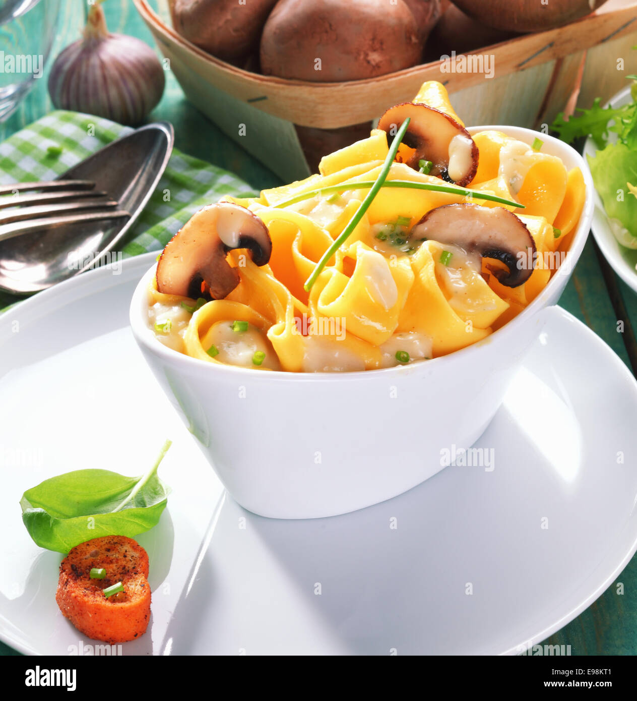 Closeup of a white boat-shaped dish of tasty tagliatelle with mushrooms - Stock Image