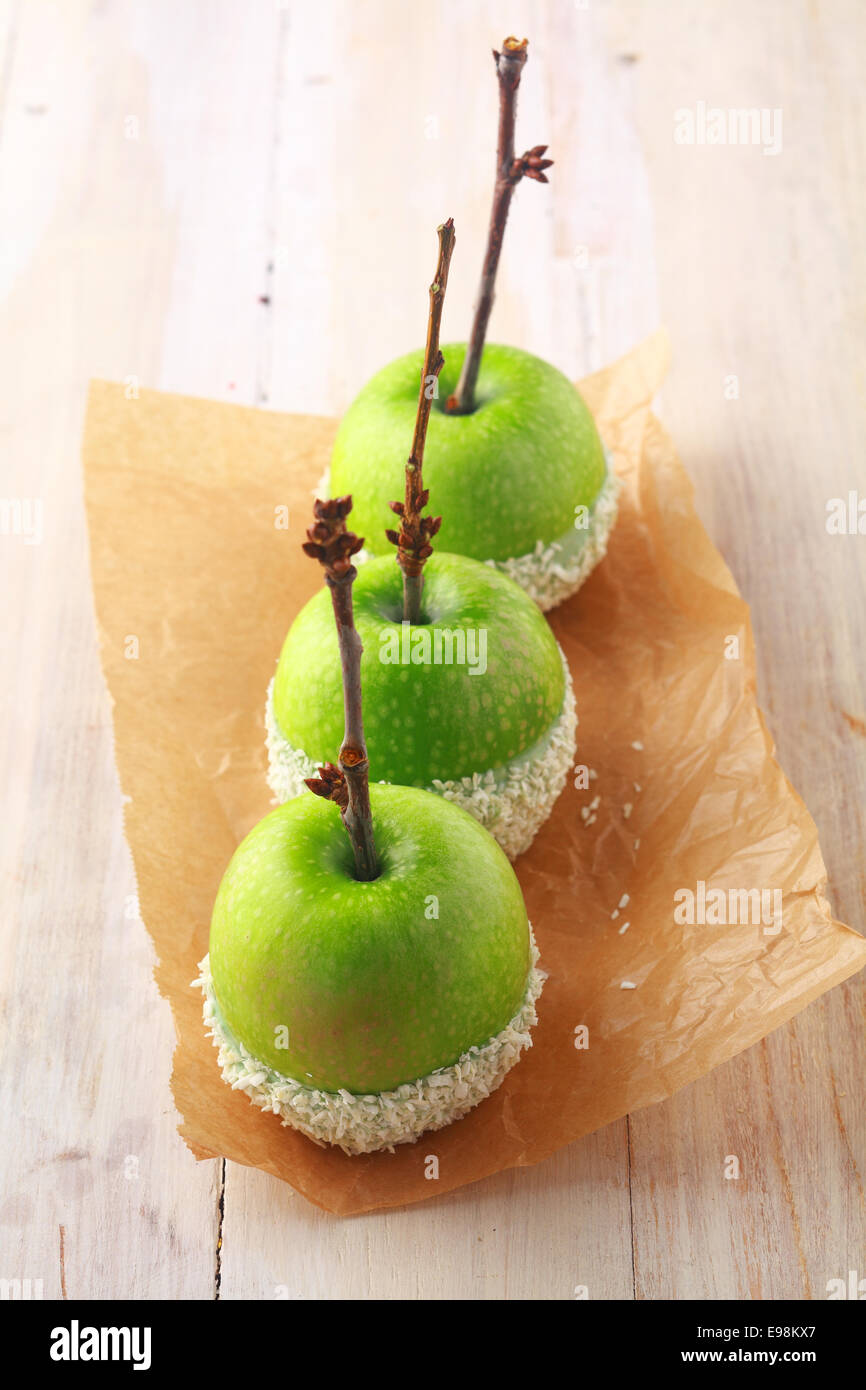 Row of fresh green apples with twigs for stems dipped in white candy sprinkles and served as Halloween favors for - Stock Image