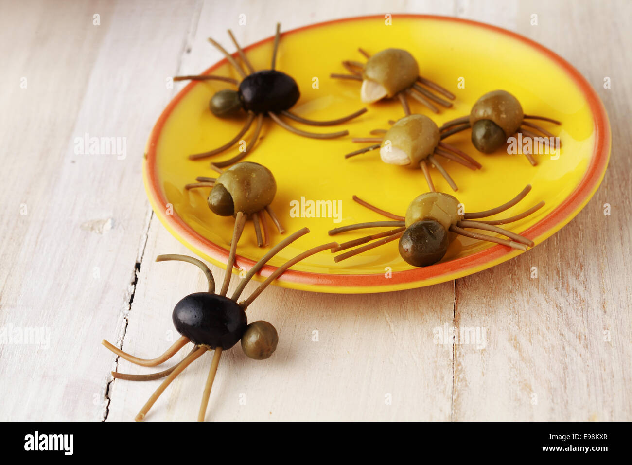 Creepy crawly Halloween spider snacks for a party celebration made from black and green olives with Italian spaghetti - Stock Image