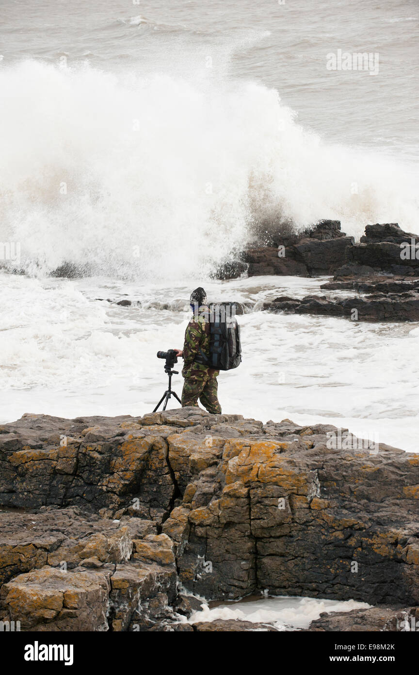 Porthcawl, Mid Glamorgan, UK. 21st October, 2014. Photographers take risks  to get good photos of waves as the evening - Stock Image
