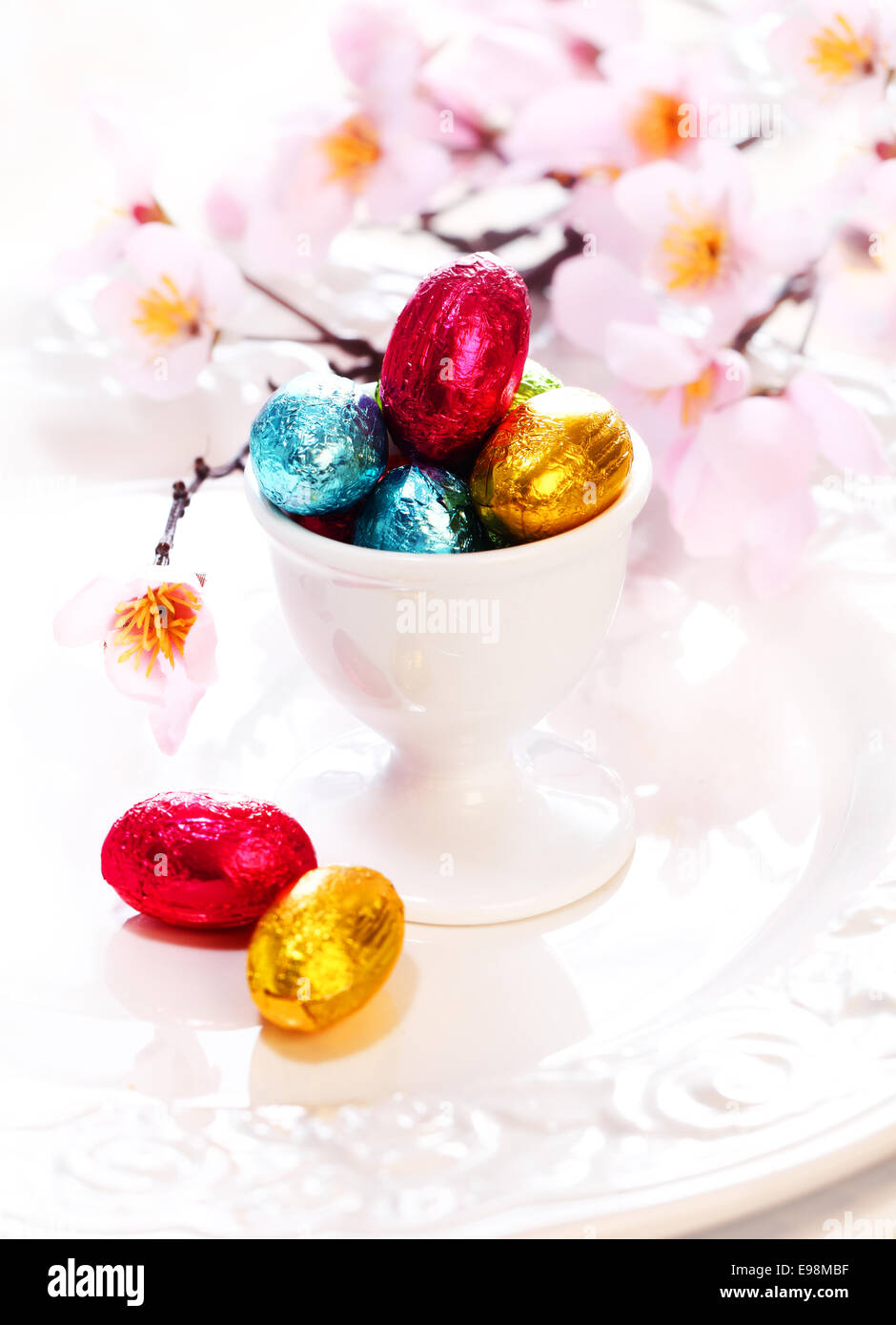 An eggcup full of tiny colourful foil wrapped chocolate Easter Eggs with cherry blossom - Stock Image