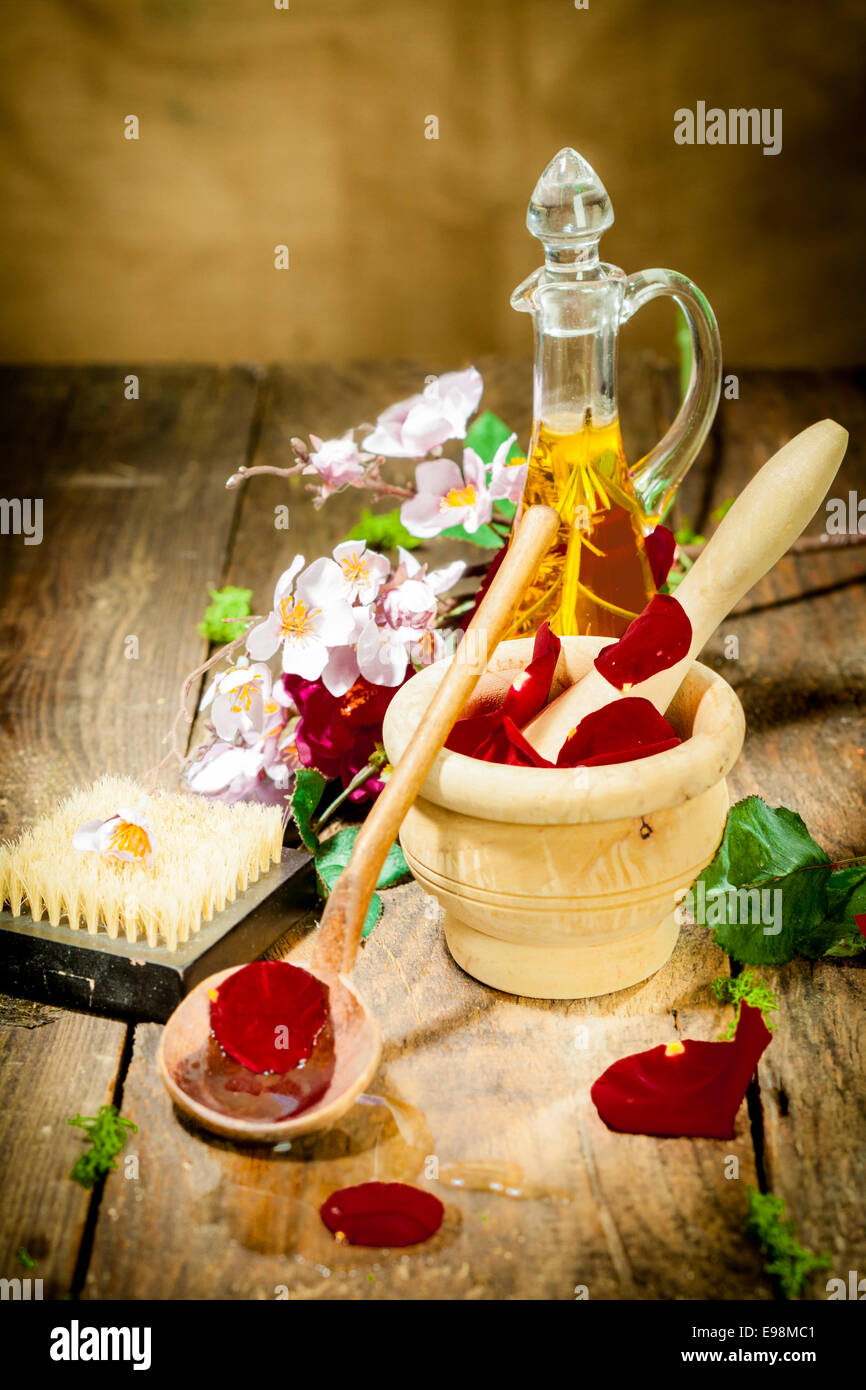 Wooden Mortar with Roses for spa and aroma therapy session on wooden floor - Stock Image