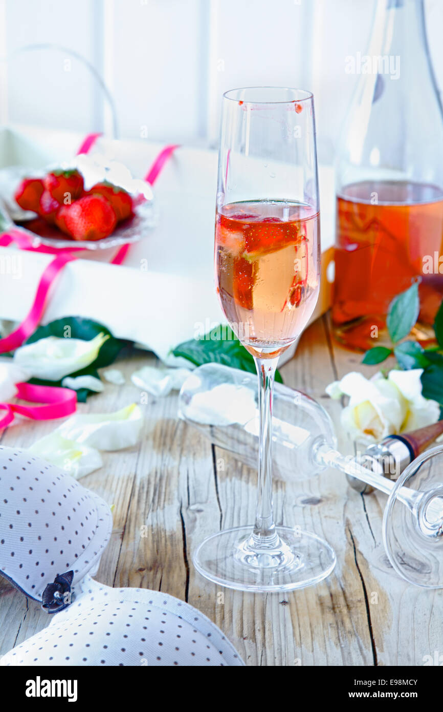 Champagne flute filled with pink champagne and strawberry pieces on a decorative table after a celebration or festivity - Stock Image