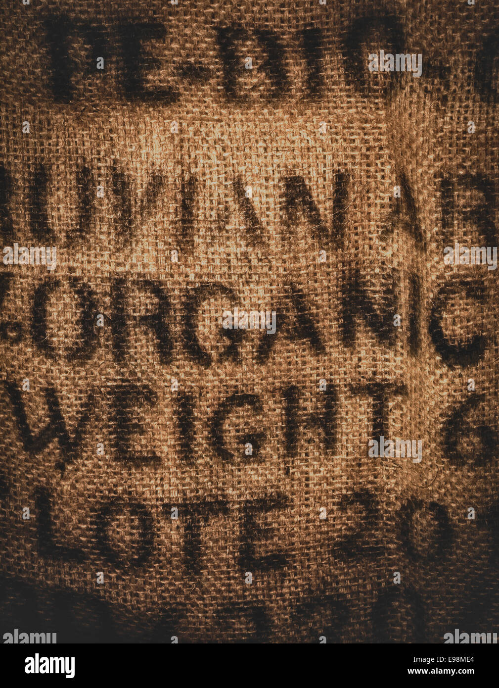 Vertical background of a twenty kilogram hessian coffee bag stamped and certified one hundred percent organic - Stock Image