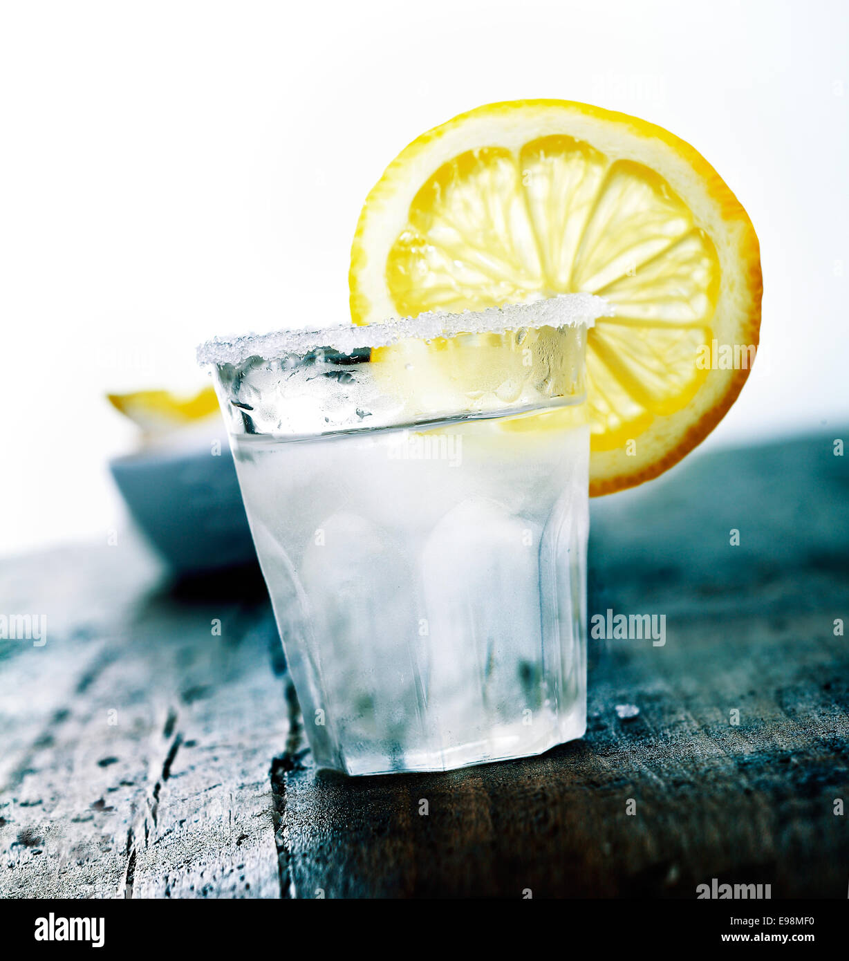 Cooled Tequila with a fresh Citron and salt on a wooden background - Stock Image