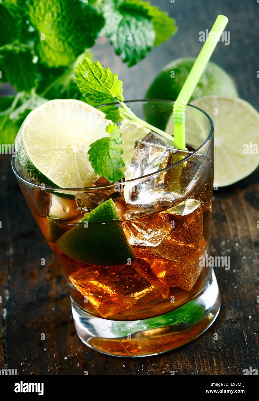 Cuba Libre Drink with lime and Cola,on a wooden plate - Stock Image