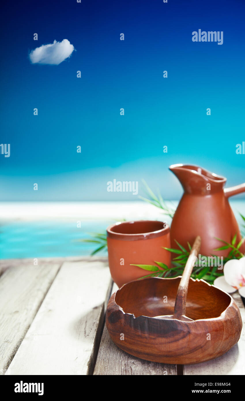 Earthenware mug and jug and small wooden bowl represent the simple cultural luxuries of traveling in tropical islands - Stock Image