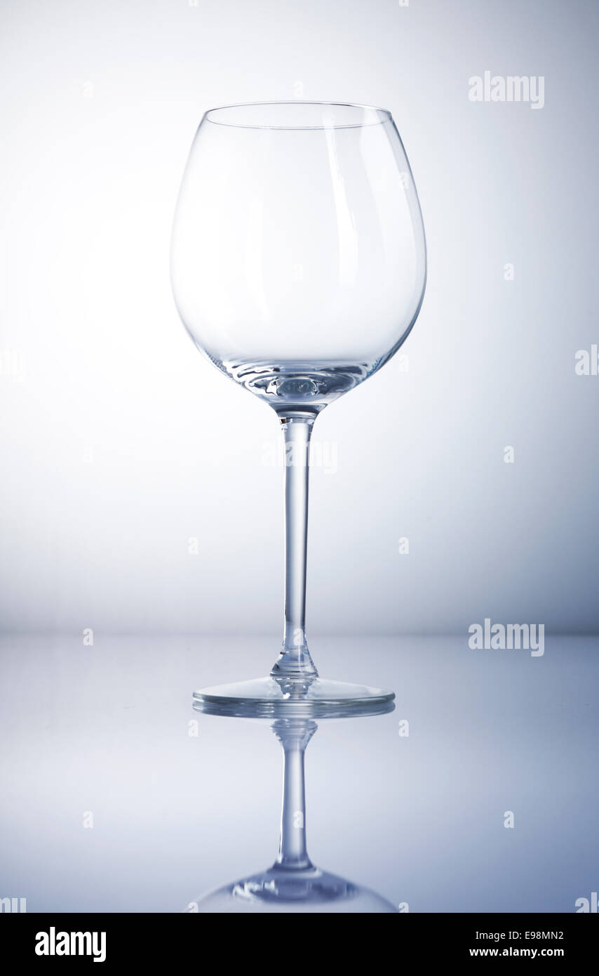 Empty wine glass with reflexion and a blue background - Stock Image
