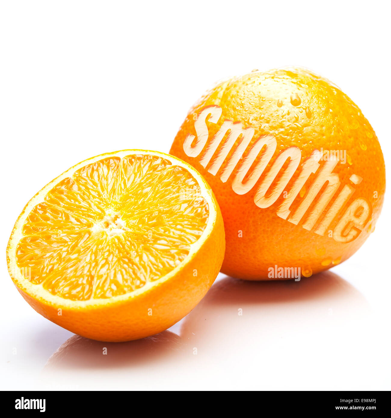 Fresh oranges with one halved to show the juicy pulp and the other whole with the word Smoothie cut out of the rind - Stock Image