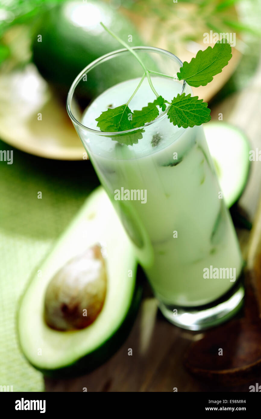 Tall glass of healthy velvety avocado smoothie rich in vitamins and monounsaturated fats - Stock Image
