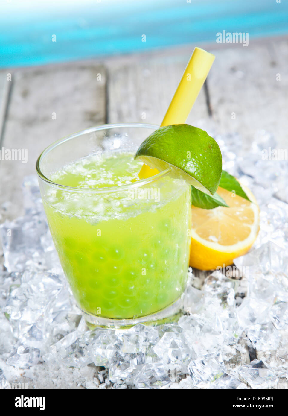 Glass of tangy refreshing lime boba tea cocktail standing on a bed of crushed ice on a wooden deck alongside blue - Stock Image