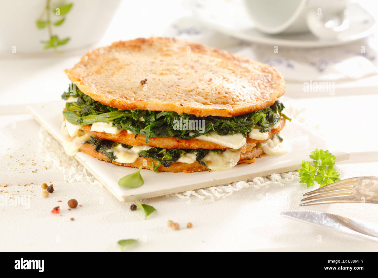 Delicios snack or light luncheon of three wholewheat pancakes stacked with a filling of cheese, spinach and greens. - Stock Image