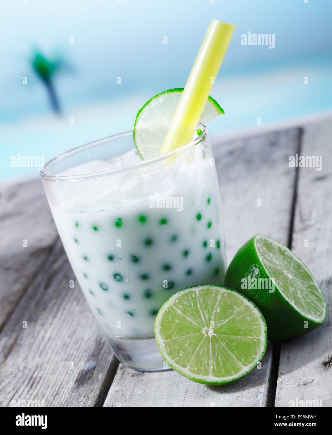 Fresh tapioka pearls tea with lime sirup standing in front of the beach on a wooden plate - Stock Image