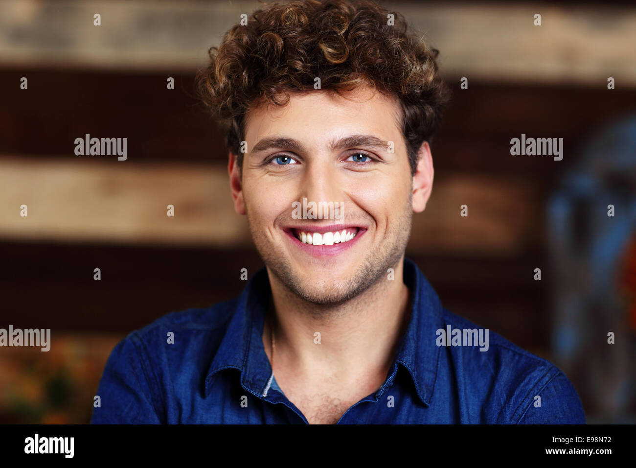 Portrait of a smiling handsome man with curly hair - Stock Image