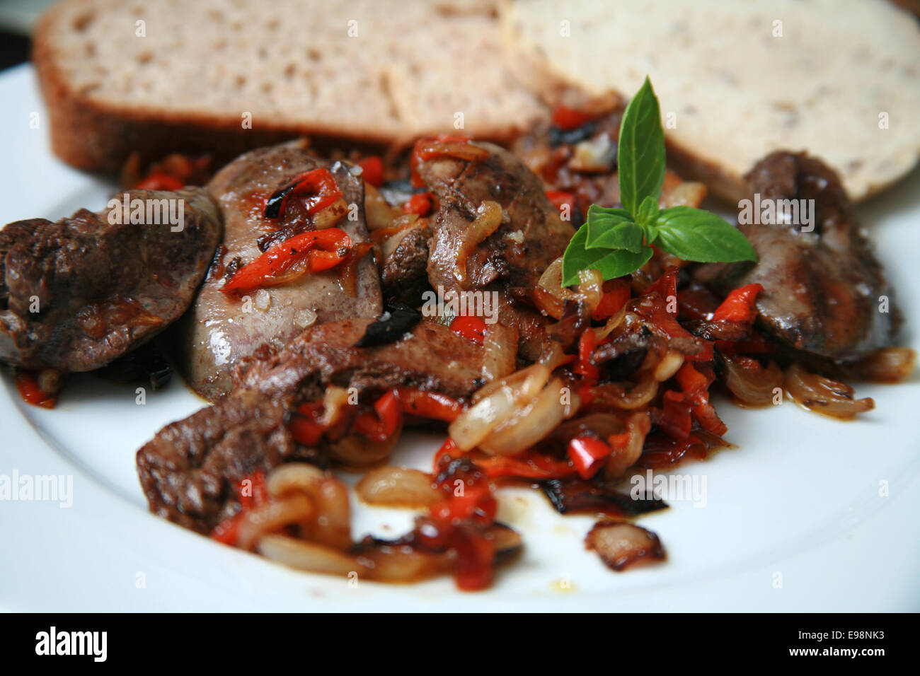 Pan fried chicken livers with caramelised onions and red peppers served on white plate with brown and rye bread - Stock Image
