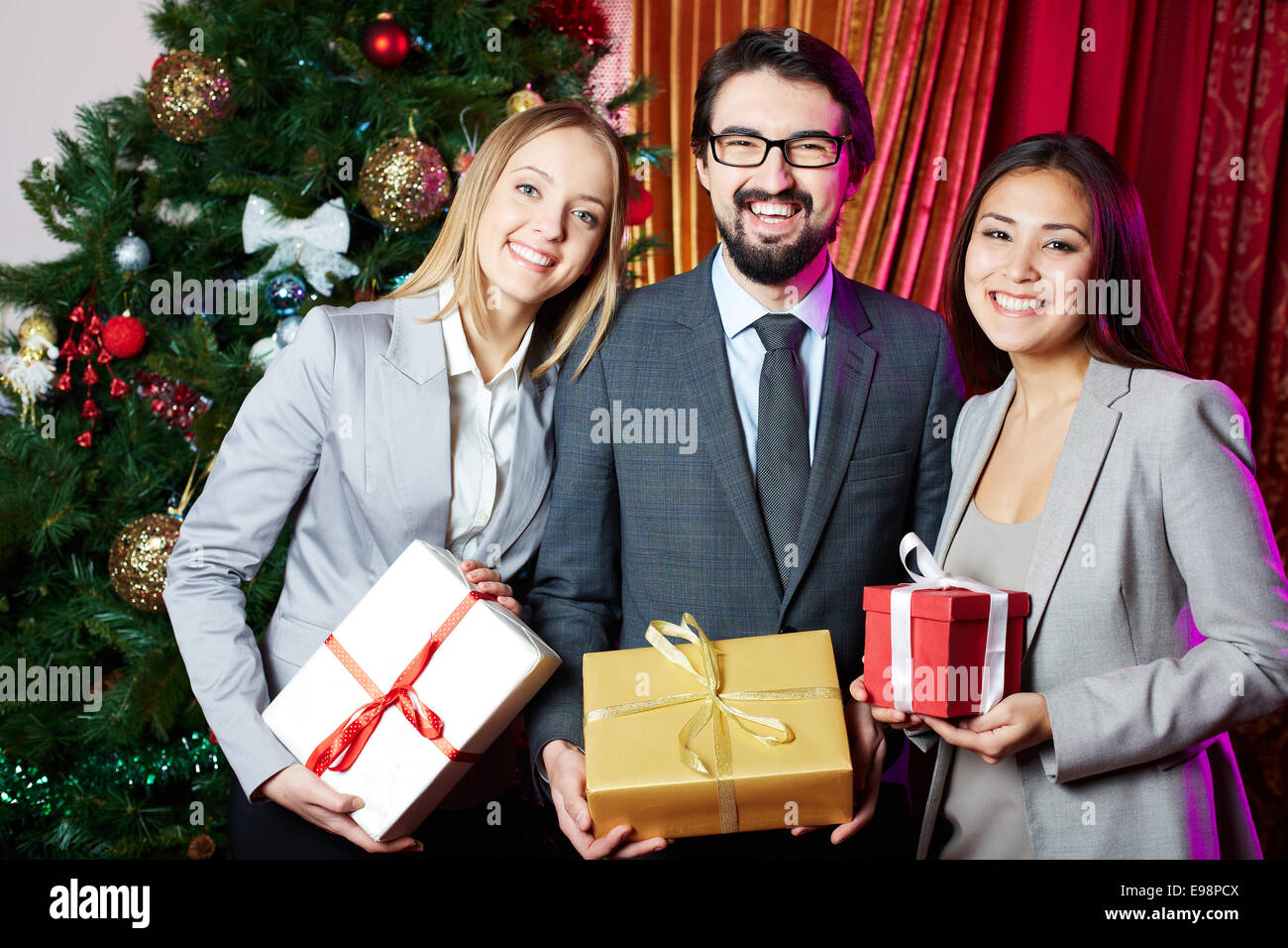Portrait of joyful colleagues with giftboxes standing by xmas tree - Stock Image