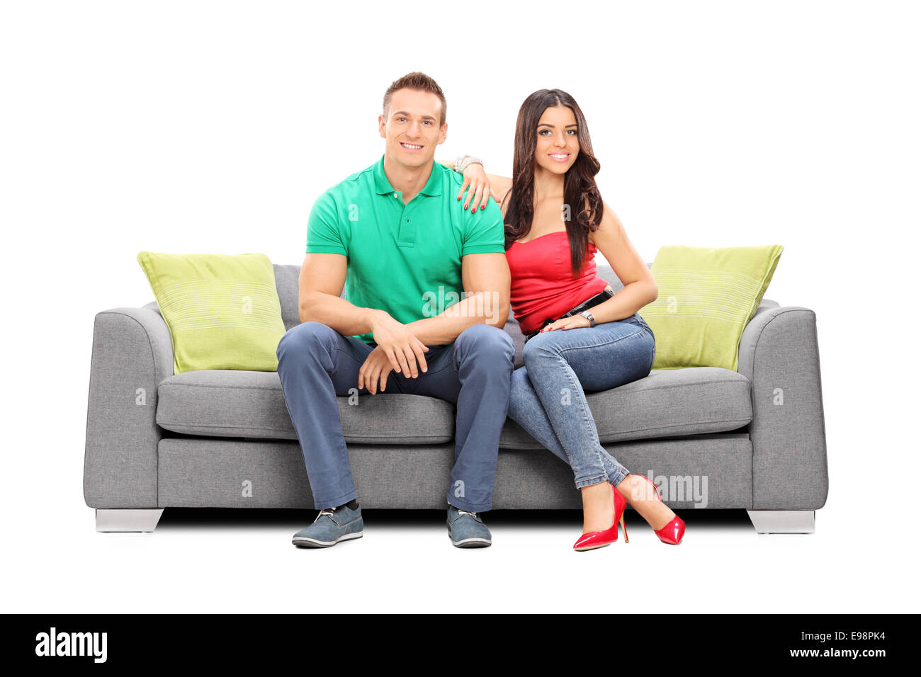 Young Couple Posing Seated On A Modern Sofa Isolated On White Stock Photo Alamy