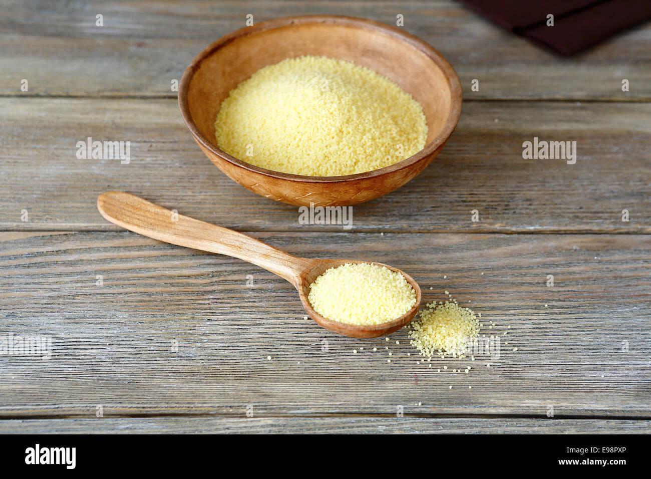 Couscous in a clay bowl and wooden spoon, food ingredient - Stock Image