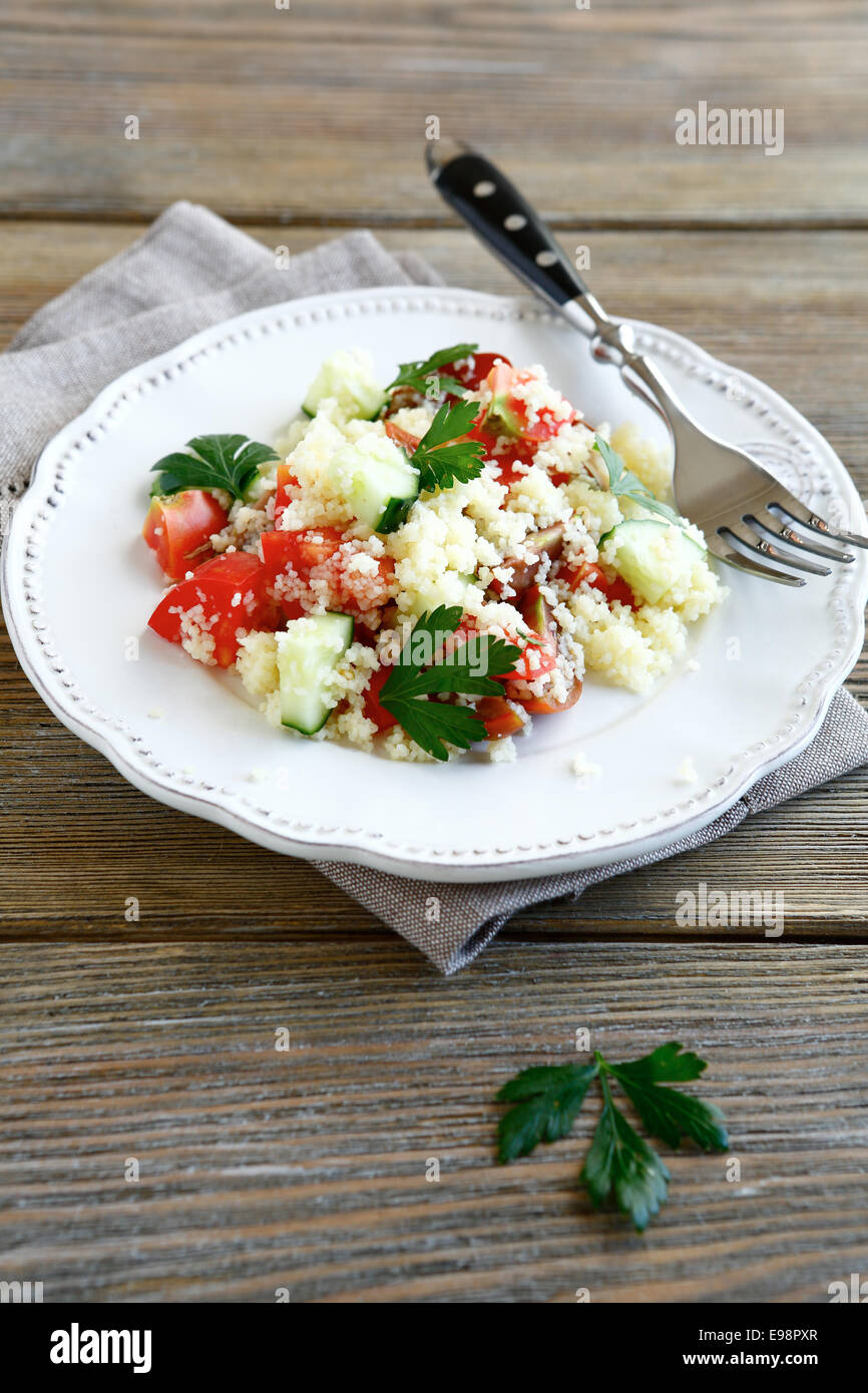 Fresh salad with arabic couscous and vegetables on a plate, delicious food - Stock Image