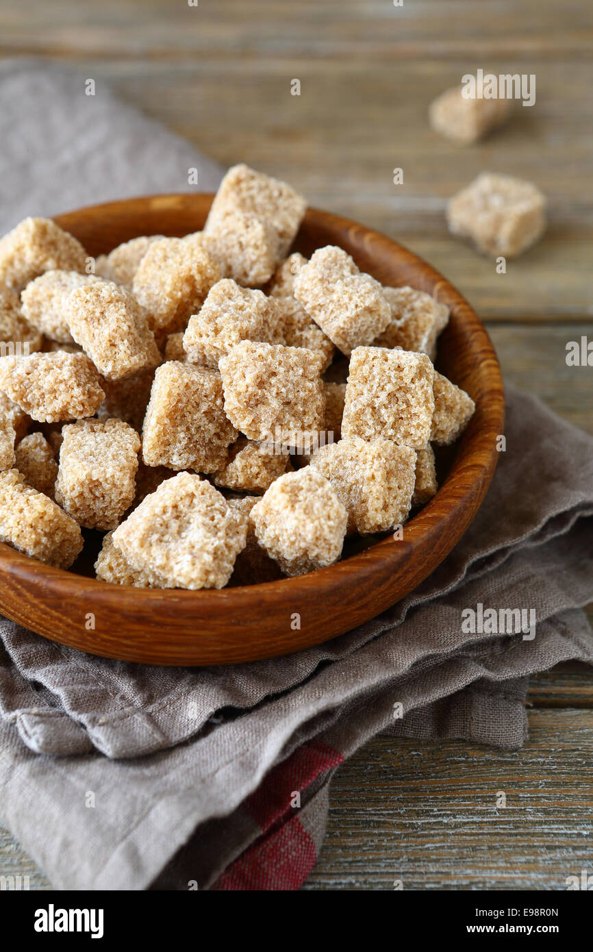 Brown sugar in a wooden bowl, side view - Stock Image