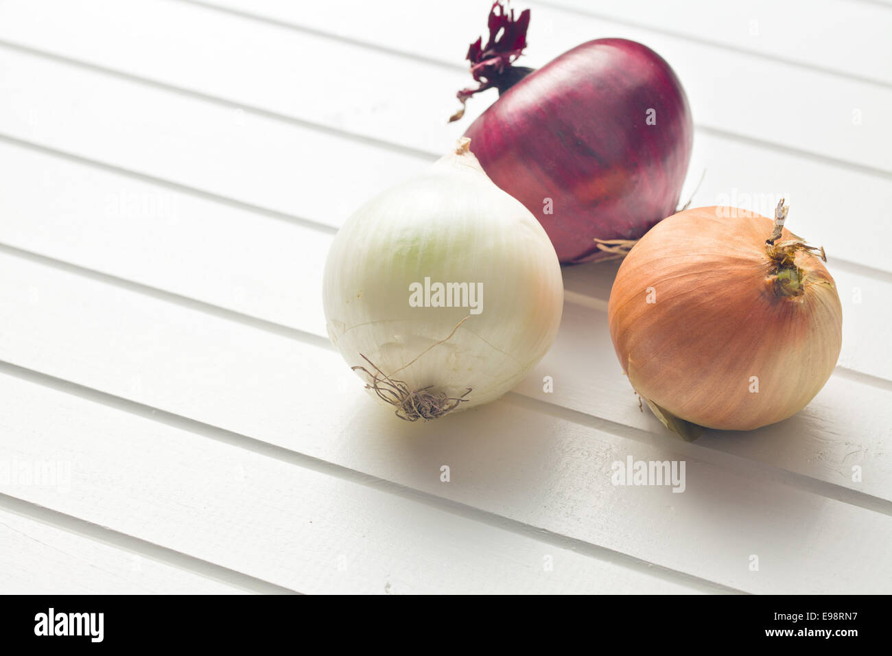 various onions on kitchen table - Stock Image