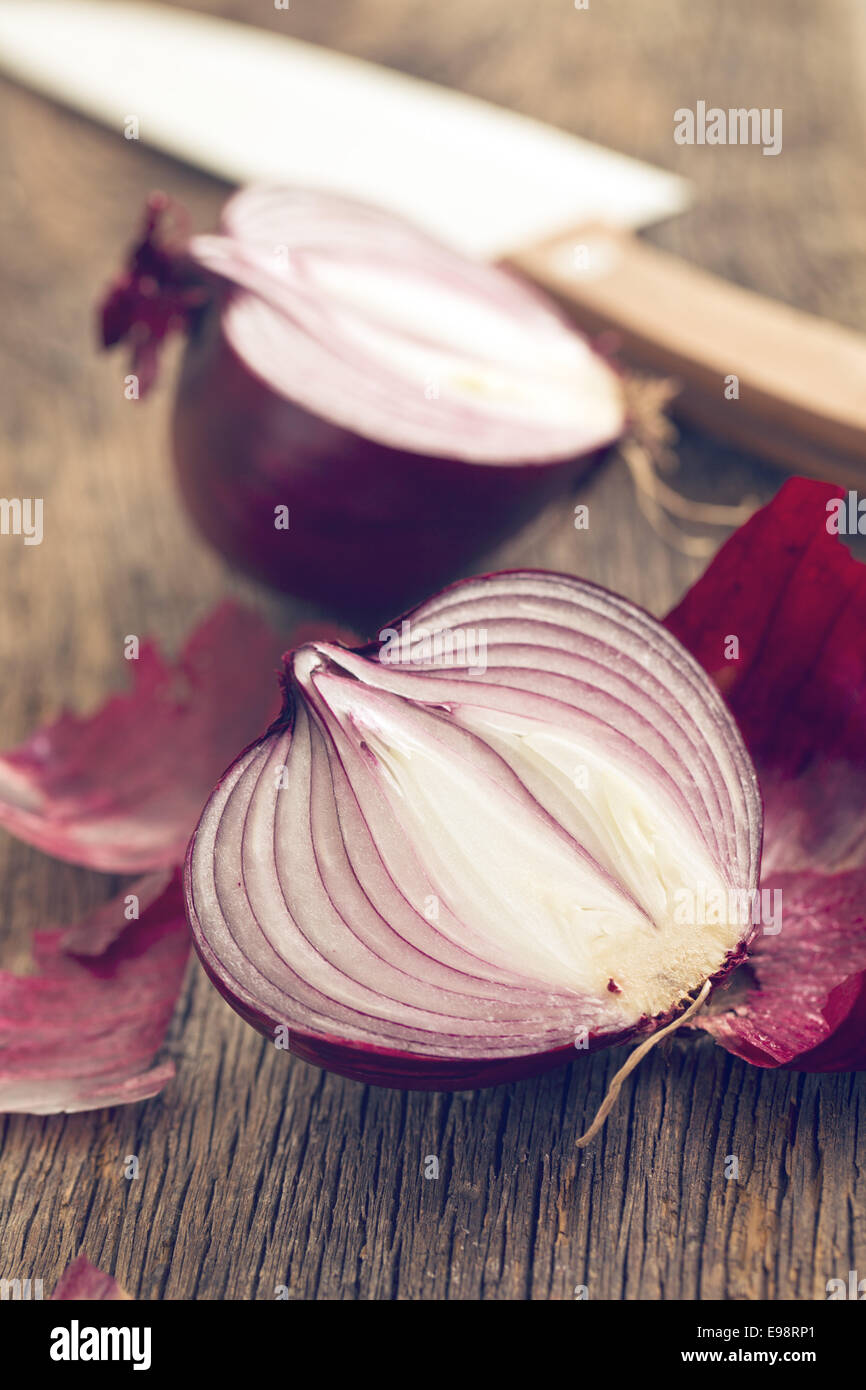 halved red onion on wooden table - Stock Image