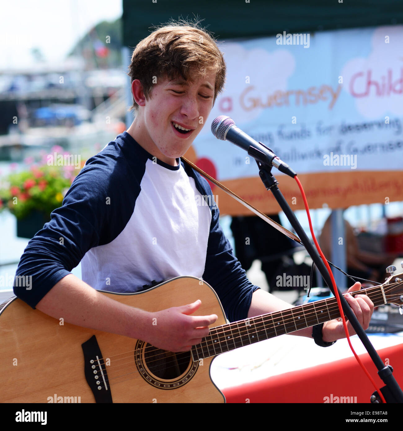 Youth playing a guitar and singing outdoors - Stock Image