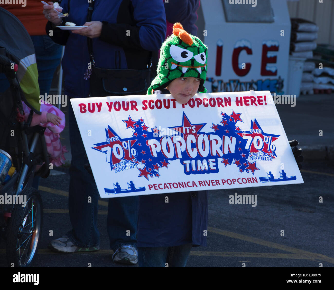 Boy scout selling popcorn at  autumn street fair - Stock Image