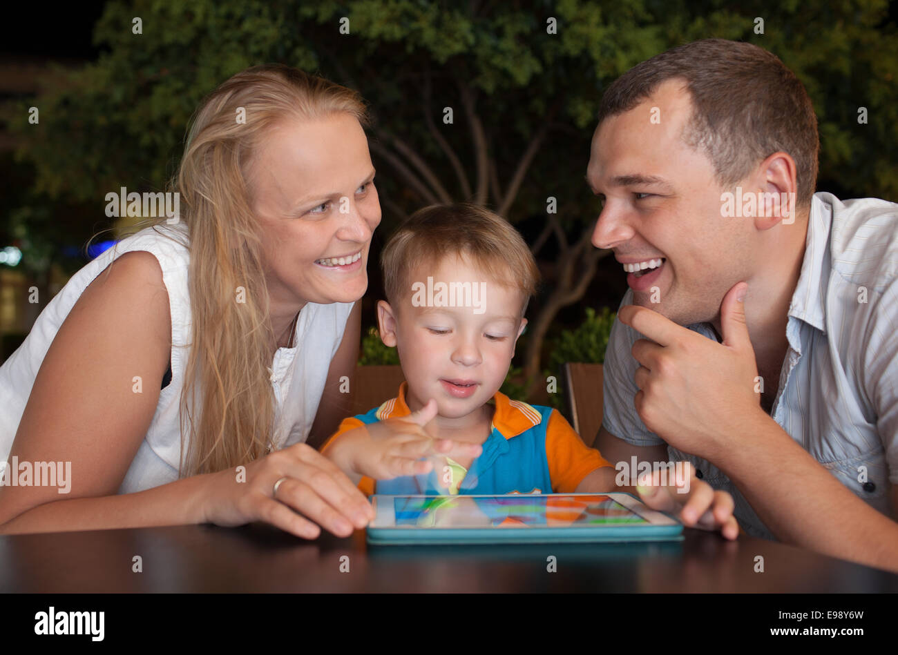 Happy family with tablet PC outdoor in the evening - Stock Image